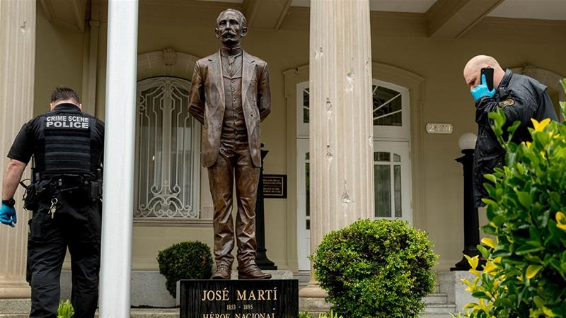 Bullet holes are visible on a column behind a statue of Cuban independence hero Jose Marti as US Secret Service officers investigate after police say a person with an assault rifle opened fire at the Cuban Embassy in the United States [Andrew Harnik/AP Photo]