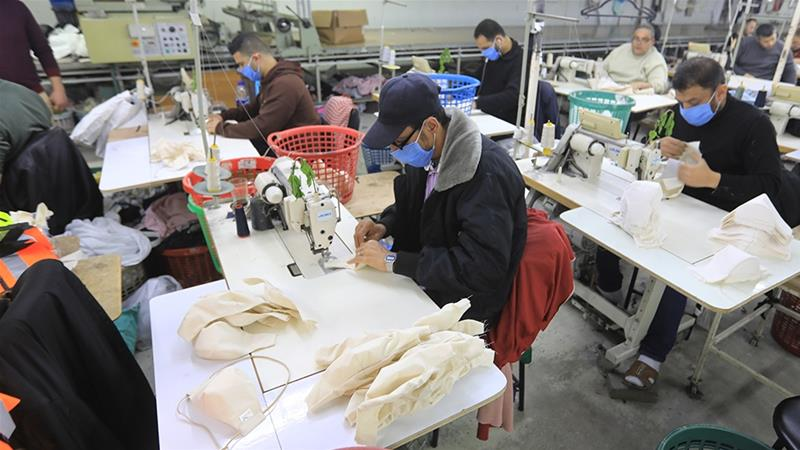 Palestinian workers make protective face masks to be exported and sold in the local market [Mahmud Hams/AFP]