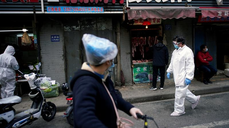 People wearing protective suits are seen at a street market in Wuhan, where the coronavirus first emerged late last year [Aly Song/Reuters]