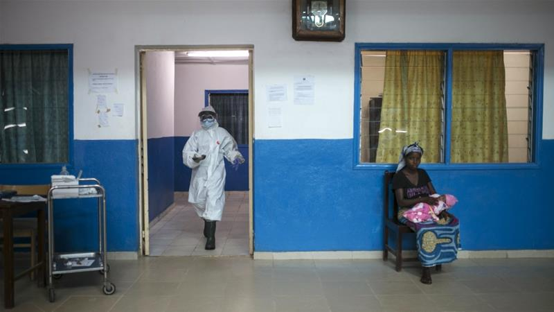 A health worker walks past a woman holding a baby at the maternity ward in the government hospital in Koidu, Kono district, in eastern Sierra Leone on December 20, 2014  [Reuters/Baz Ratner]