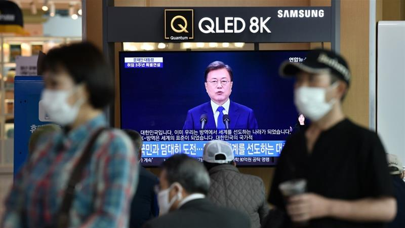 People wearing face masks watch a television news broadcast showing a speech of South Korean President Moon Jae-in at a railway station in Seoul on May 10, 2020 [Jung Yeon-je/ AFP]