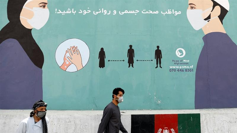 An Afghan man wearing a protective face mask walks past a painted wall amid the coronavirus pandemic, in Kabul, Afghanistan [File: Mohammad Ismail/Reuters]