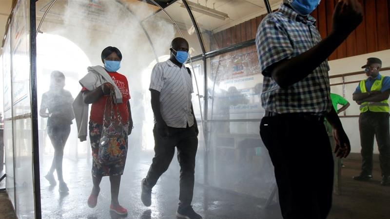 Passengers walk through a disinfectant tunnel following social distancing rules as they prepare to board a commuter train, in downtown Nairobi, Kenya April 29, 2020 [Njeri Mwangi/Reuters]