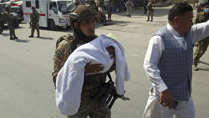 An Afghan security officer carries a baby after the May 12 attack [File: Rahmat Gul/AP Photo]
