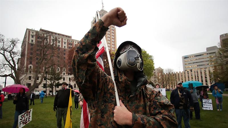 A protester raises his fist during a rally against Michigan's coronavirus stay-at-home order at the State Capitol in Lansing, Michigan [File: Paul Sancya/AP Photo]