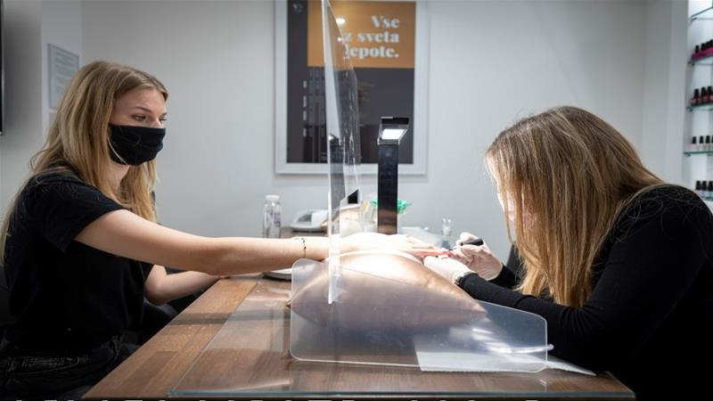 A beautician gives a manicure to a client at a beauty saloon in Ljubljana, on May 4, 2020, on the first day of the lockdown ease amid the COVID-19 pandemic caused by the novel coronavirus [Jure Makovec/AFP]