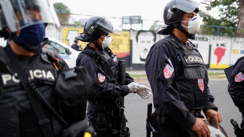 Riot police preparing to contain people who were detained for violating El Salvador's nationwide lockdown measures in San Salvador, El Salvador [Jose Cabezas/Reuters]