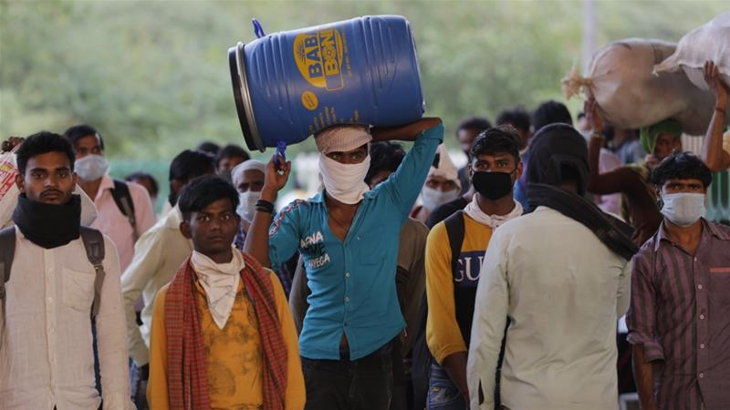 Migrant workers along with their family members walk on a road as they return to their villages during an extended nationwide lockdown to limit the spreading of the coronavirus pandemic in New Delhi [Amarjeet Kumar Singh/Anadolu]