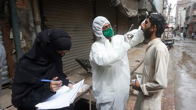 Health workers collect test samples after the government relaxed the weeks-long coronavirus lockdown, in Lahore, Pakistan [File: KM Chaudhry/AP Photo]