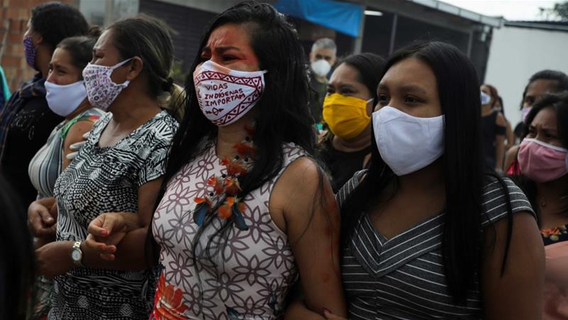 "An Indigenous woman wearing a face mask that reads, ""Indigenous lives matter"", during the funeral of Chief Messias Kokama, 53, from the Parque das Tribos (Tribes Park), who died after contracting the coronavirus at Parque das Tribos in Manaus, Brazil [Bruno Kelly/Reuters]"