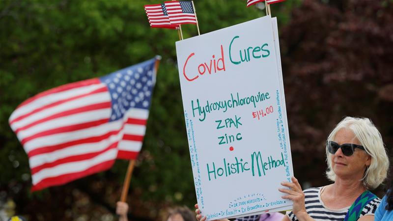 A woman holds a sign listing 'COVID Cures', including hydroxychloroquine, at a protest against coronavirus restrictions in the US state of Massachusetts [Reuters/Brian Snyder]