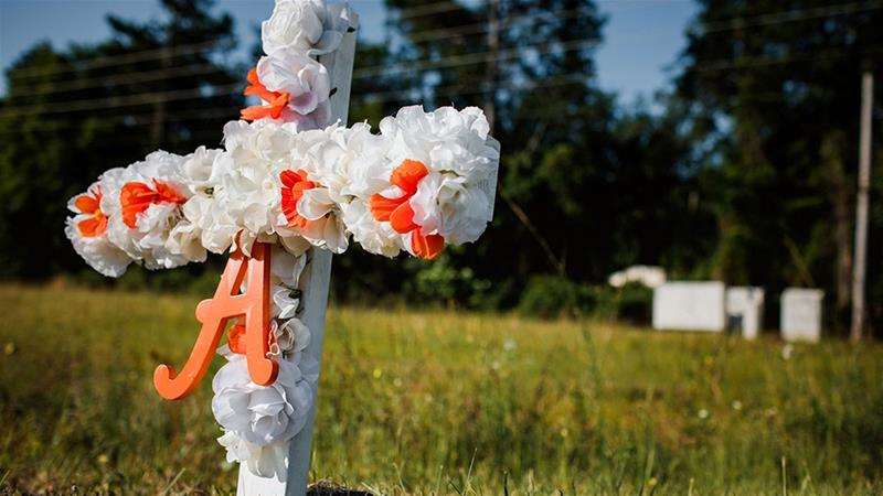 A white and orange cross with an 'A' on it stands stuck in the ground along United States Highway 17 at the entrance of the Satilla Shores neighbourhood where Ahmaud Arbery, an unarmed young black man, was killed [Dustin Chambers/Reuters]