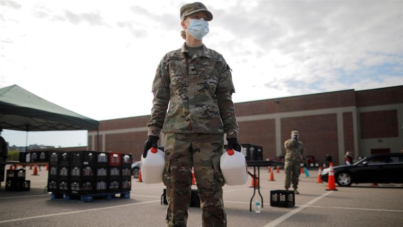 Members of the Massachusetts Army National Guard distribute free milk, offered instead of dairy farmers throwing away excess milk due to lower demand amid the coronavirus disease (COVID-19) outbreak, in Boston, Massachusetts [File:Brian Snyder/ Reuters]
