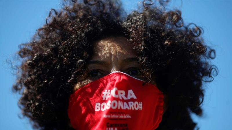 A demonstrator wearing a face mask reading 'Out Bolsonaro' during a protest against Brazil's President Jair Bolsonaro in front of the National Congress in Brasilia, Brazil [Adriano Machado/Reuters]