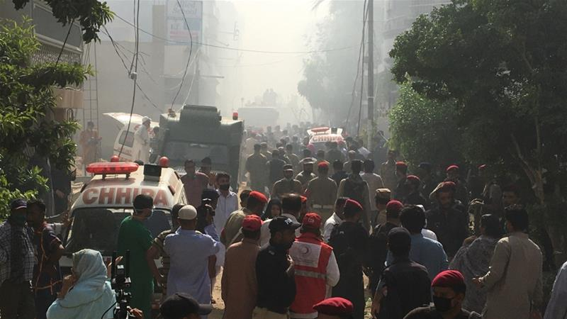 Ambulances and fire brigade vehicles gather at the site of a passenger plane crash in a residential area near an airport in Karachi [Akhtar Soomro/Reuters]
