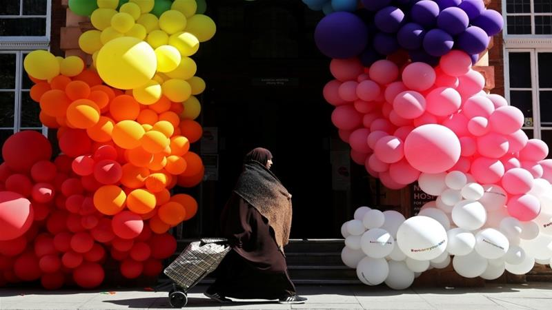 A Muslim woman walks past balloons outside London's National Hospital for Neurology and Neurosurgery as the spread of the coronavirus disease (COVID-19) continues [File: Simon Dawson/Reuters]