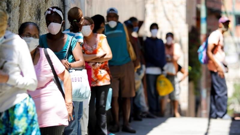 People wait in line to receive food from a charity in the neighbourhood of Carapita during a nationwide coronavirus quarantine in Caracas, Venezuela, which has so far reported 1,245 COVID-19 cases and 11 deaths [File: Manaure Quintero/Reuters]