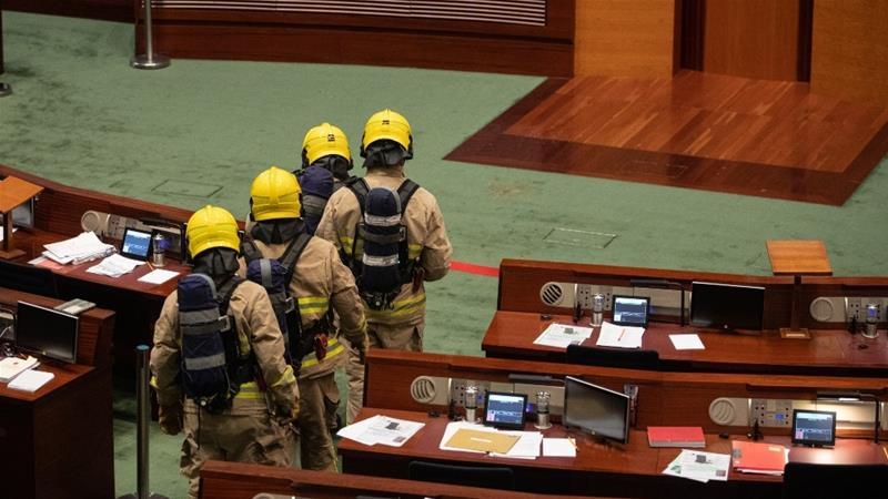 Firefighters in gas masks check the Legislative Council chamber after a pan-democrat politician threw a 'smelly object' during the second reading of the controversial national anthem bill, suspending debate [Jerome Favre/EPA]