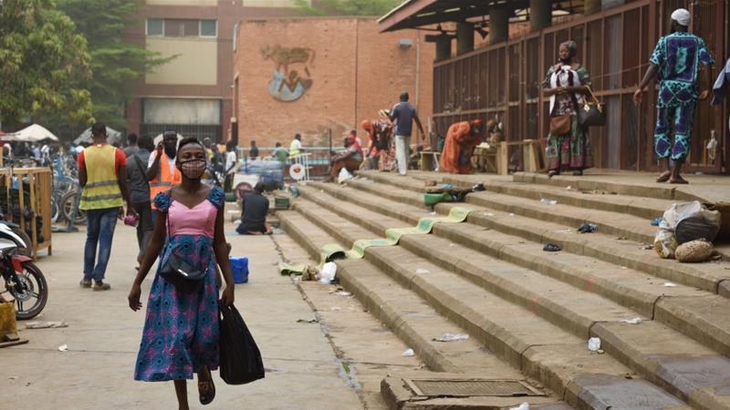 A woman walks outside the reopened Rood-Wooko market amid the spread of COVID-19 in Ouagadougou, Burkina Faso [File: Anne Mimault/Reuters]