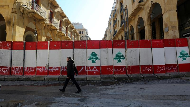 A man walks past concrete barriers erected by authorities to block a street leading to the parliament building in Beirut, Lebanon, where lawmakers on Thursday passed a law eliminating bank secrecy for officials [File: Aziz Taher/Reuters]