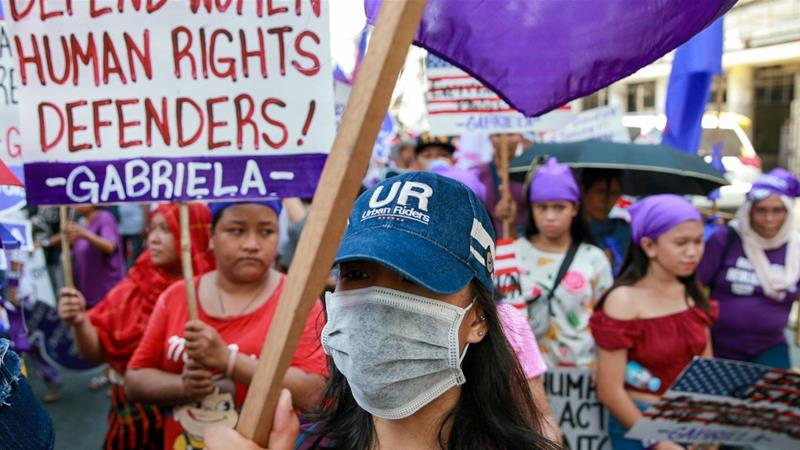 A women's rights activist wears a protective mask amid the coronavirus pandemic during a women's rights rally in Manila, Philippines, March 8, 2020 [Eloisa Lopez/Reuters]
