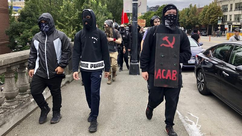 In this file photo from 2017, Anti-fascist counter-demonstrators prepare to confront the far-right group, the Proud Boys, in Portland, Oregon [Gillian Flaccus/AP Photo]