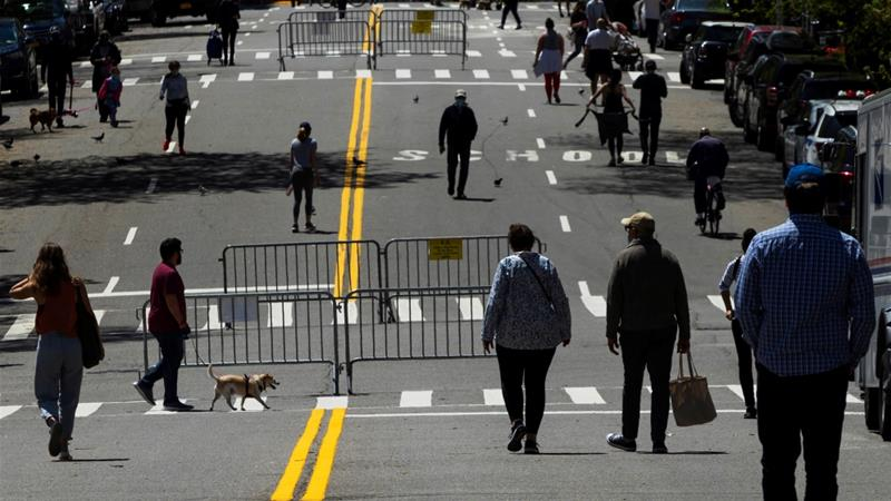Folks walking along a closed avenue in East Discontinue Avenue within the Ny borough of Fresh York Metropolis, US [Eduardo Munoz/Reuters]