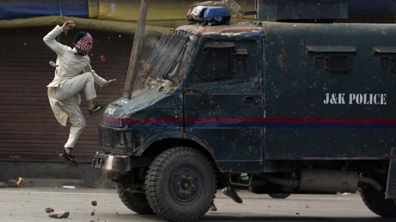 A masked Kashmiri protester jumps on the bonnet of an armoured vehicle of Indian police as he throws stones at it during a protest in Srinagar [Dar Yasin/AP]