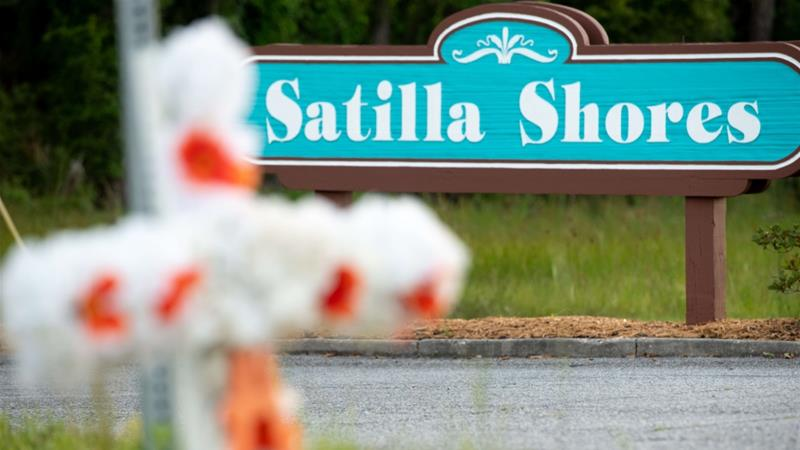 A cross with flowers and a letter 'A' sits at the entrance to the Satilla Shores neighbourhood where Ahmaud Arbery was shot and killed [Sean Rayford/Getty Images/AFP]