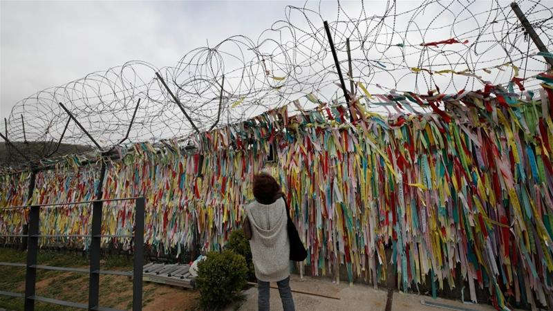 A wire fence close to the border between the two Koreas decorated with ribbons written with messages wishing for the reunification of the  peninsula [Lee Jin-man/AP Photo]