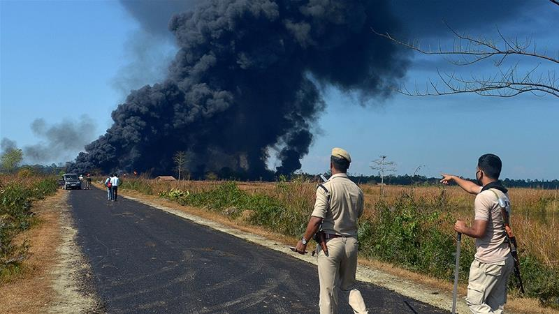 Policemen gesture as they ask people to move to a safer place as smoke rises to the sky following an explosion at an oil well in Assam [Partha Sarathi Das/AFP]