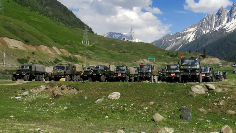 Indian army soldiers walk past their parked trucks at a makeshift transit camp before heading to Ladakh, near Baltal, southeast of Srinagar [Reuters]