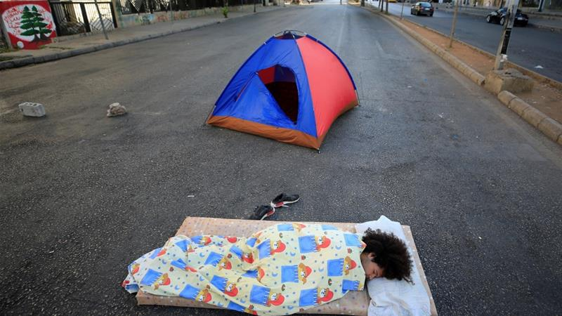 A demonstrator lies on the ground to block a road after overnight protests against fall in Lebanese pound and mounting economic hardship, in Sidon, Lebanon [File: Ali Hashisho/Reuters]