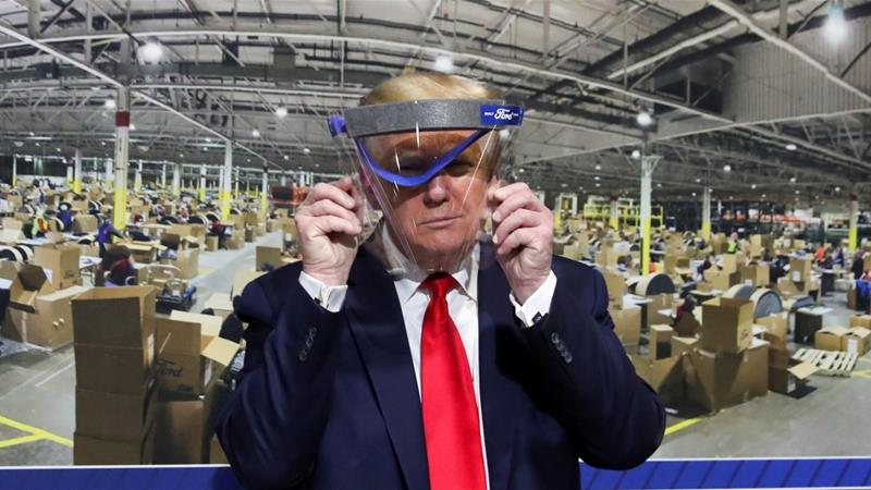 US President Donald Trump holds up a protective face shield during a tour of a Ford plant that is manufacturing ventilators, masks and other medical supplies in Michigan [File: Leah Millis/Reuters]