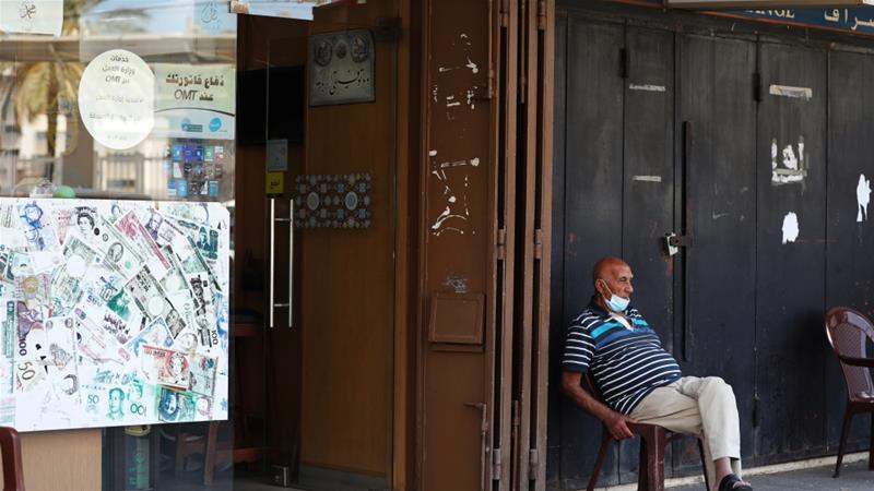 A man sits outside a currency exchange shop in Beirut, Lebanon, which is in the grips of an economic crisis rooted in years of financial mismanagement and a culture of corruption among the country's elite, as well as the war next door in Syria [File: Mohamed Azakir/Reuters]