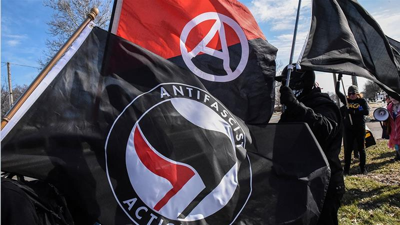 Members of the Great Lakes anti-fascist organization (Antifa) fly flags during a protest against the Alt-right outside a hotel in Warren, Michigan [File:Stephanie Keith/Reuters]