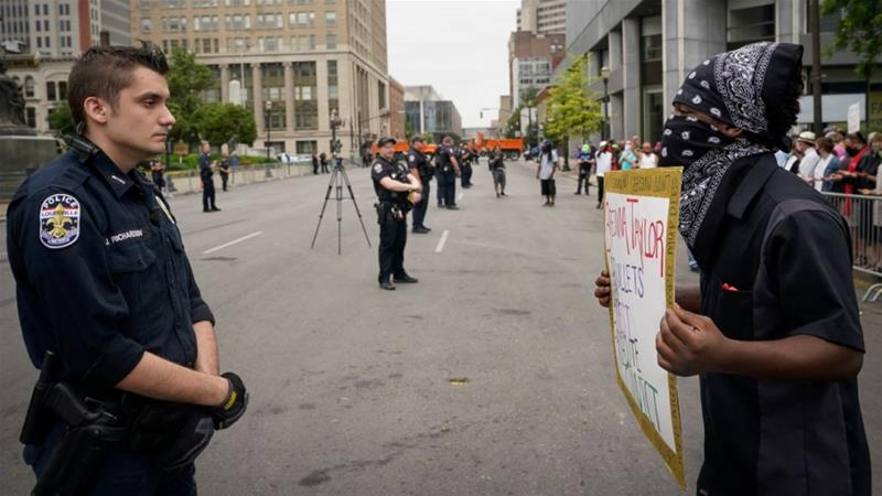A protester confronts a police officer during a rally against the death of Breonna Taylor and other forms of racial injustice in Louisville on Saturday