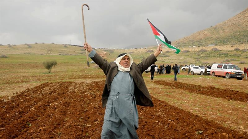 "A demonstrator holds a cane and a Palestinian flag during a protest against US President Donald Trump's ""Middle East plan"" in the Jordan Valley [Raneen Sawafta/Reuters]"