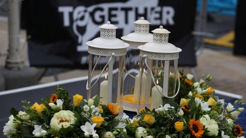 Flowers and candles are seen during a vigil in memory of the victims of the June 20 attack [Steve Parsons/Pool via Reuters]