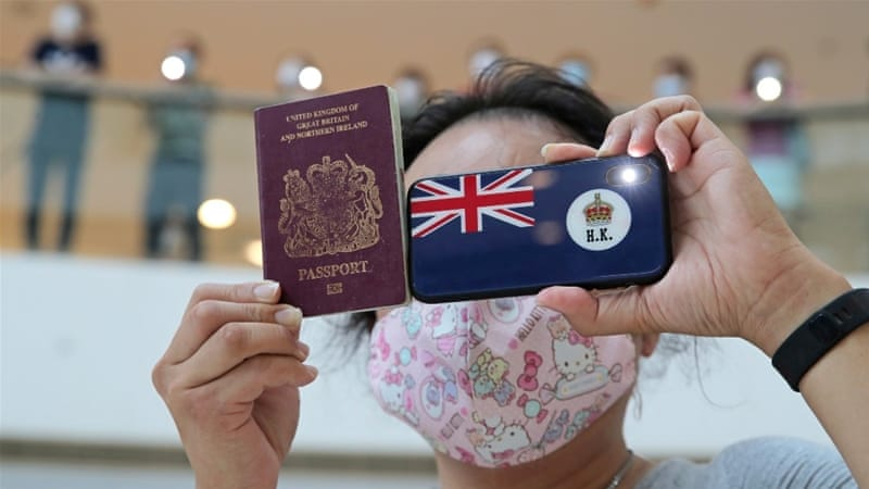 A protester holds up a British National (Overseas) passport during a protest against China''s new national security bill for the territory on May 29 [Kin Cheung/AP Photo]