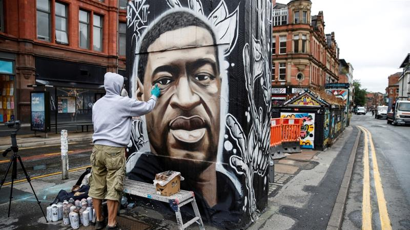 Artist Akse works on a mural of George Floyd who died in police custody in Minneapolis [Phil Noble/Reuters]