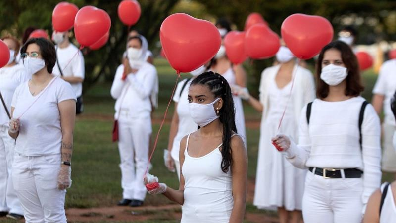 A group of artists perform 'who left is someone's love' to pay tribute to the victims of the coronavirus in Brasilia [Joedson Alves/EPA]
