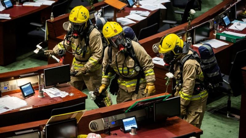 Members of the fire brigade conduct decontamination work in the main chamber of the Legislative Council after pan-democrat legislators hurled an odorous liquid during the third reading of the national anthem bill in Hong Kong on June 4, 2020 [Isaac Lawrence/ AFP]