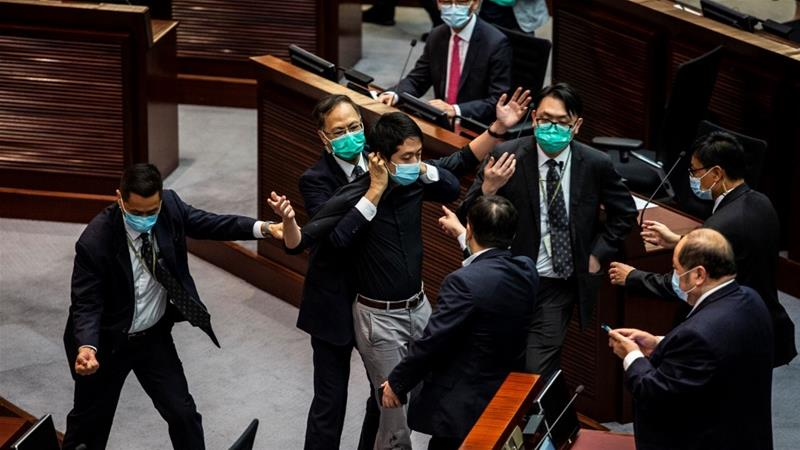 Legislator Ted Hui, centre, is removed by security guards after throwing a jar containing a four-smelling liquid onto the floor [Isaac Lawrence/ AFP]