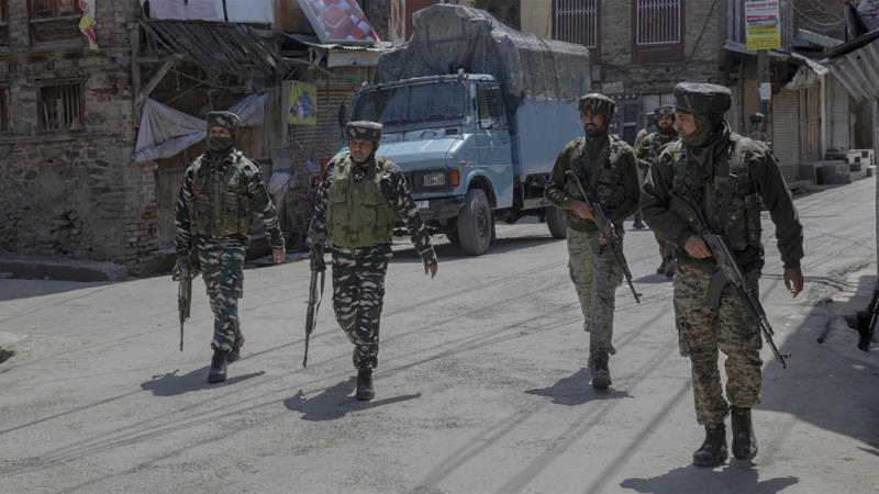 Indian paramilitary soldiers walk back towards their vehicles after a gun battle [Dar Yasin/AP]