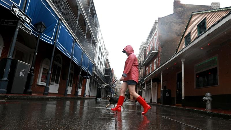 A woman walks her dog through the French Quarter as Tropical Storm Cristobal nears the coast on June 7 in New Orleans, Louisiana [Sean Gardner/AFP]