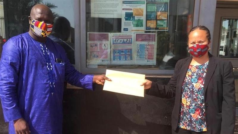Activist Madi Jobarteh hands a petition calling for a thorough investigation of Momodou Lamin Sisay to Rebecca McKnight, the regional security officer of the US embassy in Banjul [Courtesy of Madi Jobarteh/Al Jazeera]