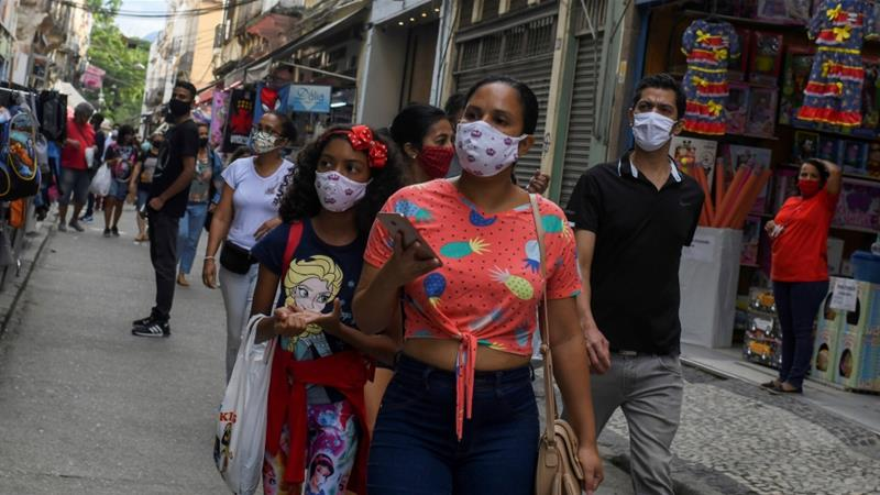 People wear protective masks as they walk at a popular shopping street, as the city eases restrictions and allows commerce to open, amid the coronavirus disease (COVID-19) outbreak in Rio de Janeiro, Brazil [Lucas Landau/Reuters]
