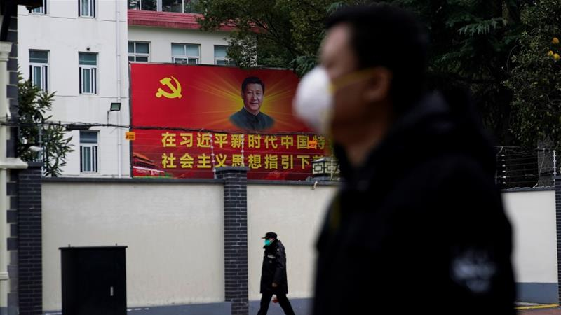 People wearing masks walk past a portrait of Chinese President Xi Jinping on a street amid the coronavirus pandemic in Shanghai [File: Aly Song/Reuters]