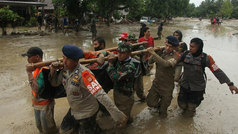 A rescue team carry a victim's body following flash flooding in Radda village in North Luwu district [Aryanto / AFP]